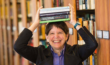 Woman in library holding books on her head