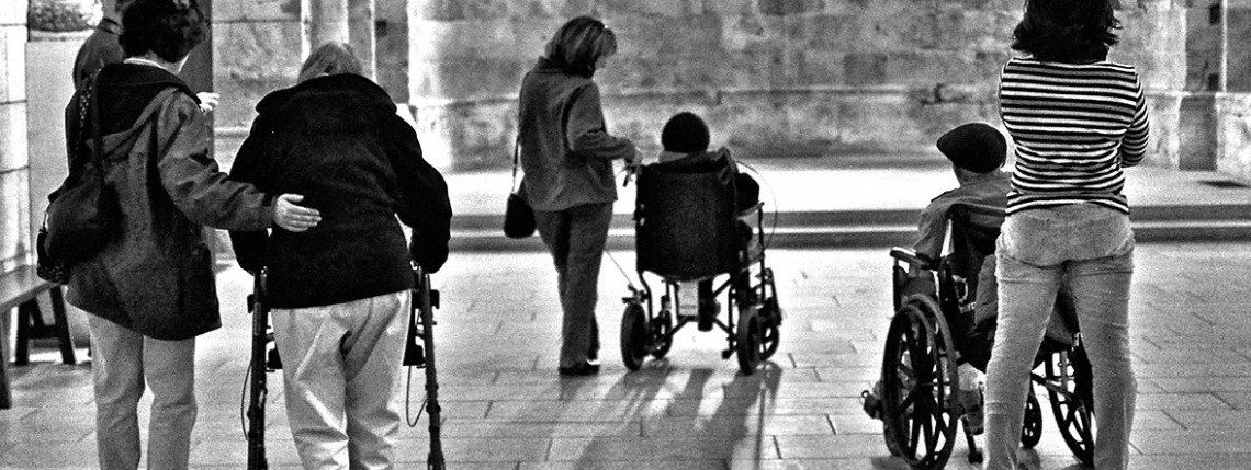 People assisting other who are in wheelchairs or walkers