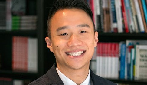 Man in suit smiling in library