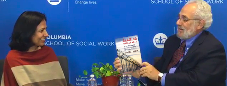 """Neeraj Kaushal with her book """"Blaming Immigrants"""""""